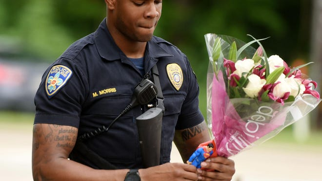 Baton Rouge Officer Markell Morris holds a bouquet and a Superman action figure left by a citizen at Our Lady of the Lake Hospital, where the police officers shot on Sunday were taken.