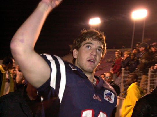 Ole Miss QB Eli Manning waves to the fans while walking off the field after their victory over Nebraska in the 2002 Independence Bowl.