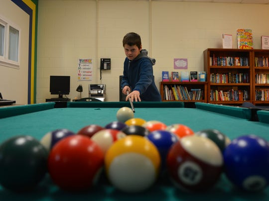 Fourth-grader Dylan Arvey plays pool at the Carver Cove.