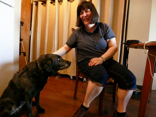 "Joanne Stark pats her guide dog ""Ditra"" Thursday at"