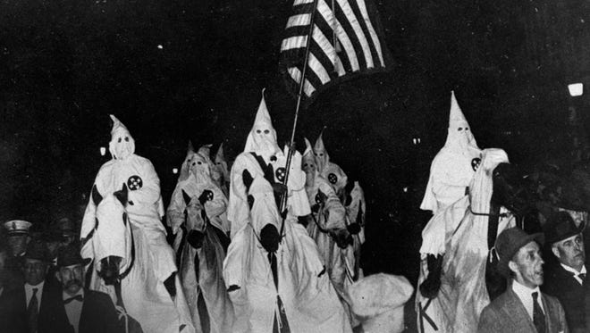 In this 1923 photo, members of the Ku Klux Klan ride horses during a parade through the streets of Tulsa, Okla.