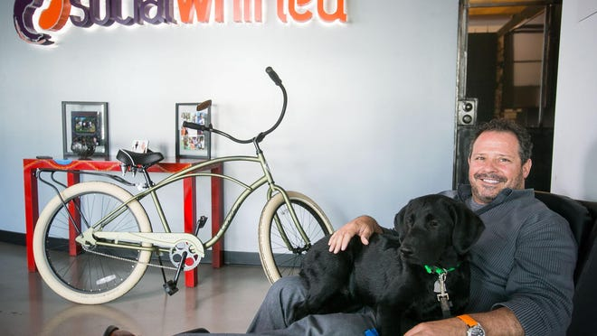 CEO and co-founder Andrew Lombard with his dog at the offices of SocialWhirled in central Phoenix on Wednesday, May 27, 2015.