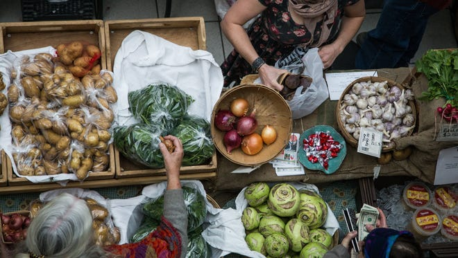 Emily Hutchinson, at top, sells produce to customers at a winter farmers market in 2015.