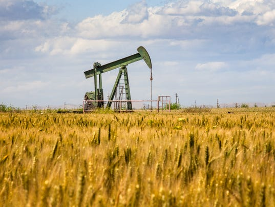 Lone Oil Pumpjack Amidst A Field of Golden Wheat