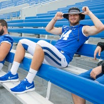 Kentucky quarterback Patrick Towles takes a seat in the stands with teammates while waiting for team portraits during media day.