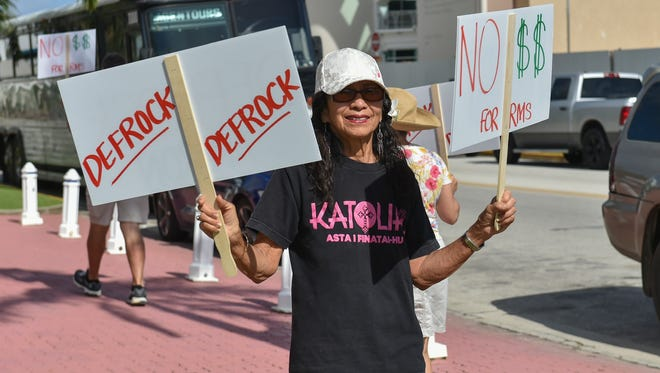 """Laity Forward Movement member Lou Klitzkie protests with signs reading: """"Defrock Apuron"""" and """"Hon - No $$ For RMS"""" at Dulce Nombre de Cathedral Basilica in Hagatna on Aug. 21."""