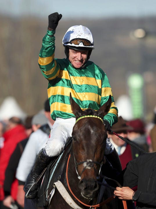 Barry Geraghty celebrates victory in the Champion Hurdle on Buveur D'Air  at Cheltenham Racecourse, Cheltenham England Tuesday March 13, 2018. (David Davies/PA via AP)