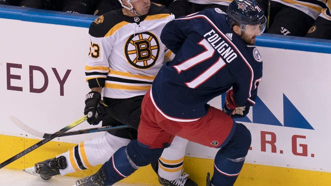 Boston Bruins left wing Brad Marchand (63) gets run into the boards by Columbus Blue Jackets left wing Nick Foligno (71) during the first period of an exhibition NHL hockey game Thursday, July 30, 2020 in Toronto.