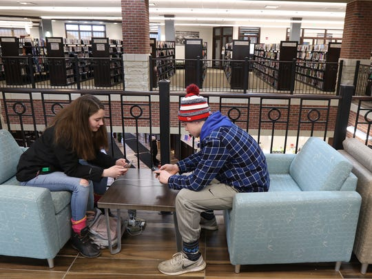 Siblings Kara Davis, 16, and Ryan Davis, 14, charge up their phones and text with their friends while waiting for their mother to come back.  Their home was without power and their mother had dropped them off at the library to go pick up firewood.