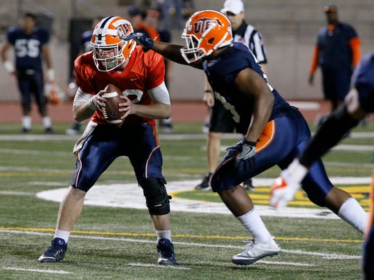 UTEP senior quarterback Ryan Metz prepares to hand the ball to wide receiver Alan Busey during the teams scrimmage held Friday night at the SISD Student Activities Center.