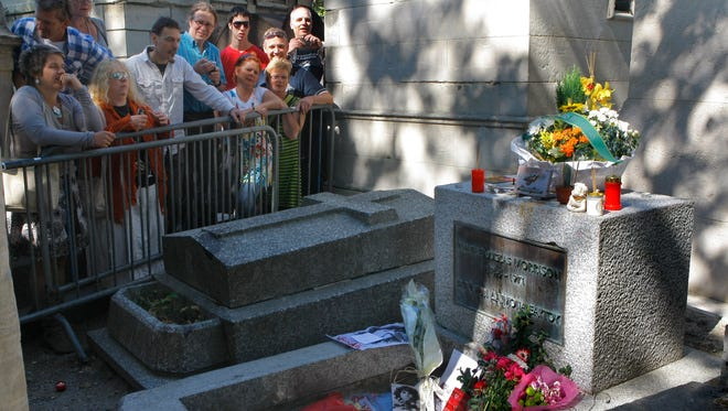 Fans of the Doors' lead singer and poet Jim Morrison pay homage at his gravesite in the Pere Lachaise Cemetery in Paris on July 3, 2011. Morrison died in Paris on July, 2, 1971.