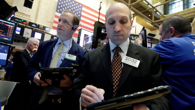 Traders Michael Smyth, left, and James Denaro work on the floor of the New York Stock Exchange, Wednesday, April 6, 2016. Stocks are wobbling in early trading Wednesday. Health care companies are trading higher, energy companies are rising along with the price of oil and telecommunications companies are slipping.