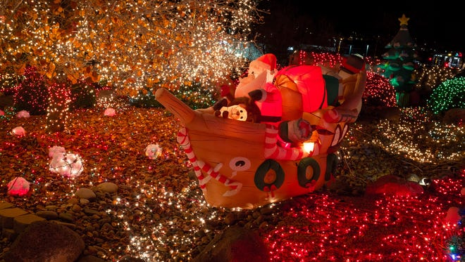 Santa Claus sails down an arroyo in the front of Dan Wasser's house as part of Wasser's elaborate Christmas decorations. There used to be two Santas in boats sailing in the display but one was stolen at the beginning of the month.