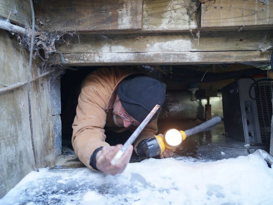 Paul McConnell, who slid into a crawlspace partially flooded with frozen water, holds up a shard of ice as he exits the cellar at a Georgetown home on Thursday, Feb. 19, 2015. The home's water pipes froze, then burst, during a spell of record cold temperatures.