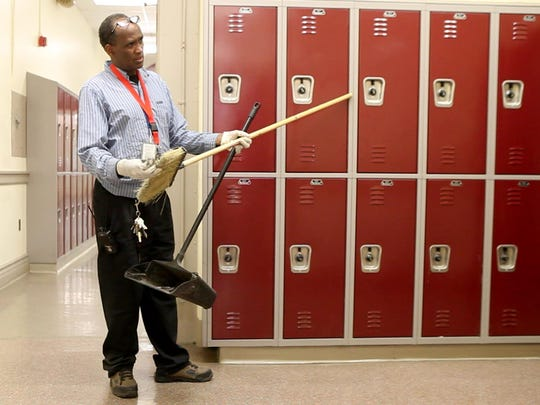 Jamal Abdullahi cleans the floors at Wilson Magnet