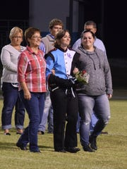 Band senior Brooklyn Yates proudly makes her way across the field with her escorts.