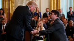 President Donald Trump shakes hands with acting Department