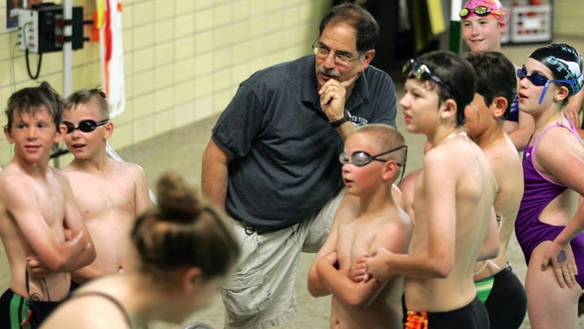 Coach Lonny Kerman meets with swimmers on the first day of a North Side Otters swim team clinic in 2012 at the North High School pool, now called the Lonny Kerman Natatorium. The local swimming community has been rallying to support Kerman who was diagnosed with stage 4 bone cancer shortly after Thanksgiving.