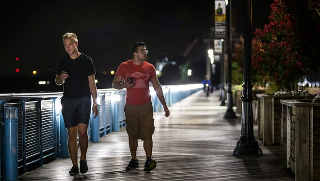 Matt Jacobs and Josh Garcia play Pokemon Go as they walk along the Riverfront Walk in Wilmington on Tuesday night.