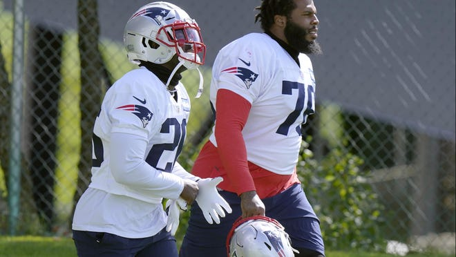 New England Patriots running back Sony Michel, left, and offensive lineman Isaiah Wynn walk to the field for an NFL football training camp practice, Wednesday, Aug. 26, 2020, in Foxborough, Mass.