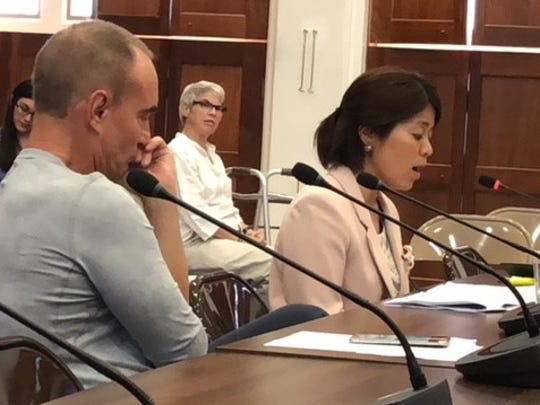 In this June 2018 file photo, Dr. Kozue Shimabukuro, right, reads her written statement alleging mismanagement, corruption and politicking at Guam Memorial Hospital, while Dr. Jerone Landstrom, left, looks on, during a public hearing on a bill seeking to repeal a 2 percent sales tax.