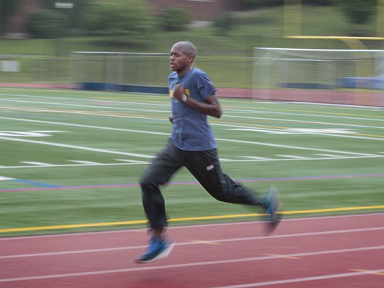Kip Tisia is a blur of grace and speed as he runs on the track at the University of Rochester.