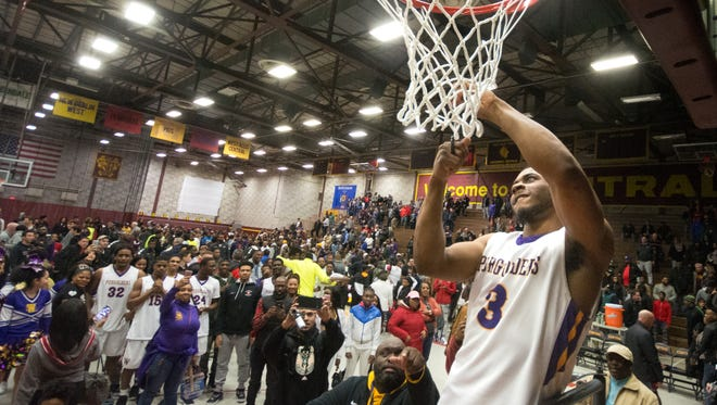 Washington players and fans watch senior guard Akier McKinney cut down the net after the Purgolders beat Pewaukee, 77-67, in a WIAA Division 2 boys basketball sectional final Saturday at West Allis Central.