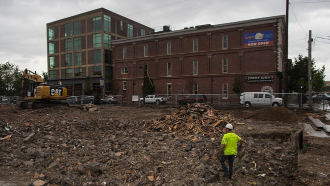 Construction crews work on cleaning up debris after the demolition of the former Connection bar building on Floyd Street to make way for the new Cambria Hotel. May 30, 2018