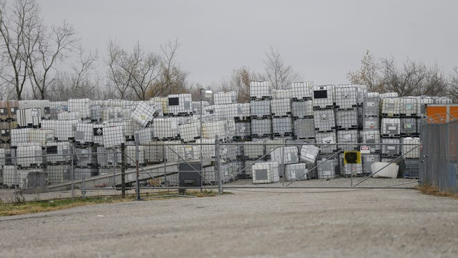 Large chemical containers are stacked outside IndyDrum in Indianapolis. The plant refurbishes or recycles the totes that have contained a wide variety of chemicals. In 2010, employees told an OSHA inspector they had seen all kinds of chemical reactions such as smoke, crackling, spattering and bubbling of liquids, while they processed the containers.