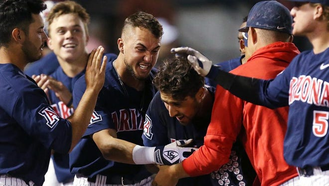 Arizona Wildcats mob their teammate Alfonso Rivas (25) after he scored the go-ahead run during the seventh.