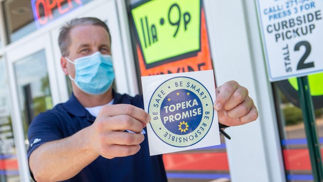 """Jason Lehnherr, Glory Days Pizza branch owner, holds up the Topeka Promise decal Thursday afternoon outside of his restaurant at 1033 S.W. Gage Blvd. The Topeka/Shawnee County Community Recovery Taskforce announced its """"Topeka Promise"""" initiative that businesses can apply for in helping to safely open businesses back up during the COVID-19 pandemic."""