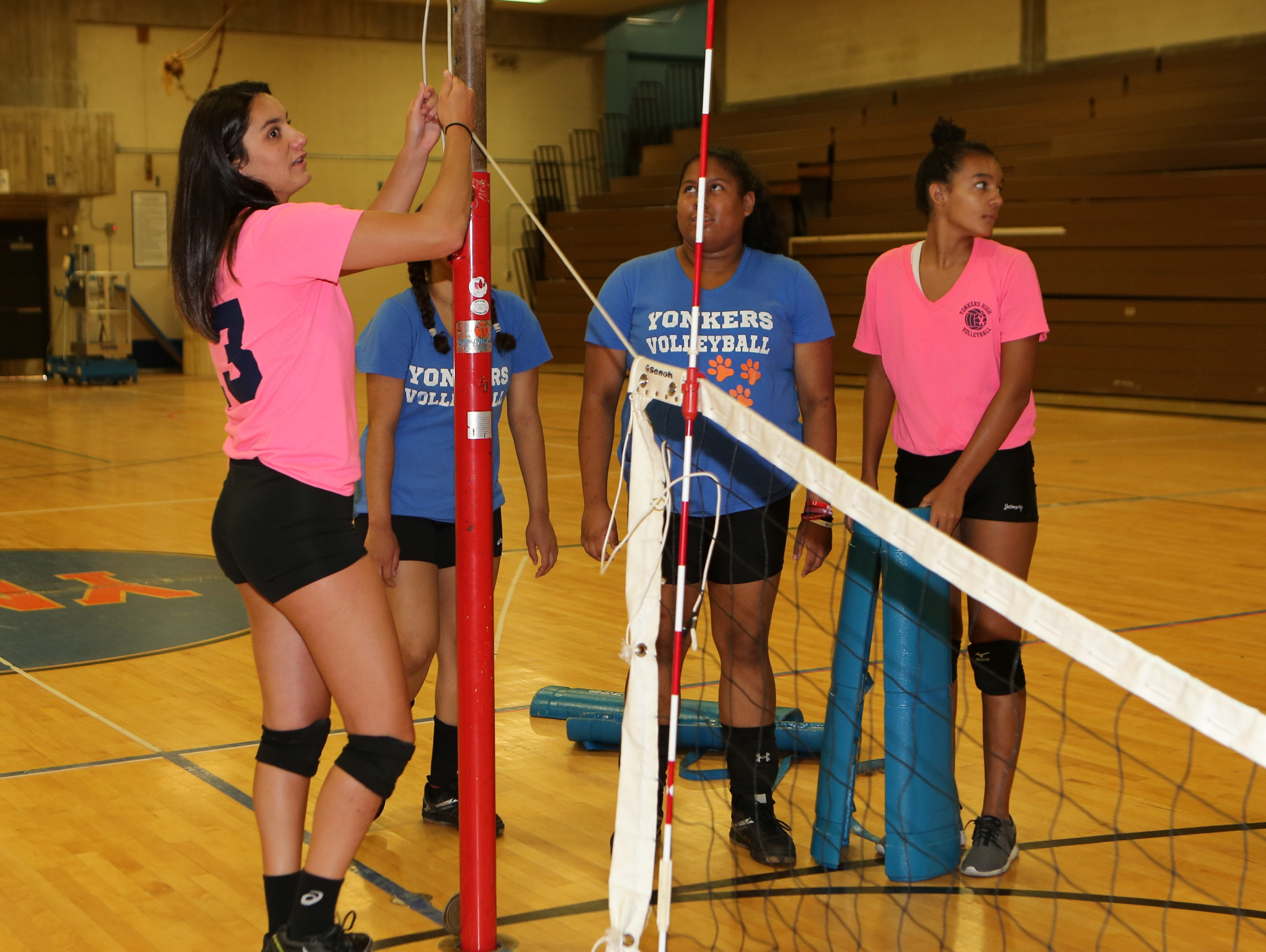 Nicole Frascati, left, a senior volleyball player at Yonkers Middle High School, helps set up a net at the school, Aug, 25, 2016.