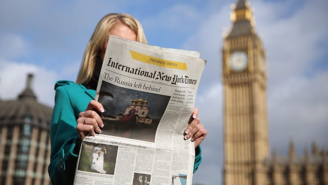 The premiere edition of the International New York Times read in Parliament Square in London on Oct,15, 2013.