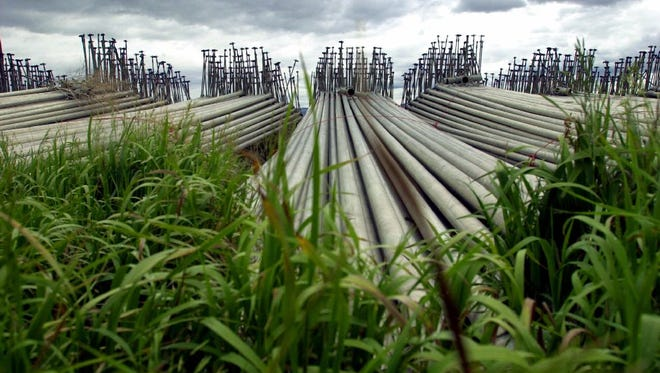 Piles of sprinkler pipes sit in an overgrowth of weeds on a farm near Tulelake, Calif.