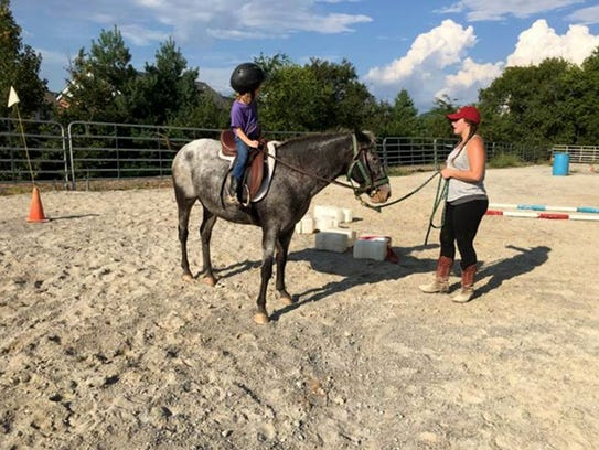 Campers learn horseback riding safety and posture,