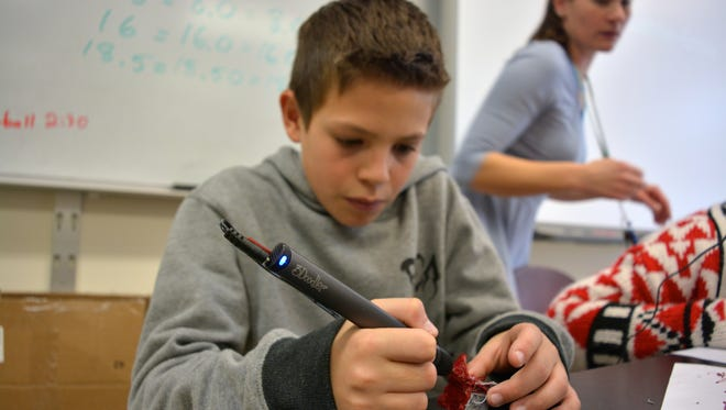 Riley Neall uses a 3-D pen to create a structure during Emily Lehne's science class at Beacon Middle School.