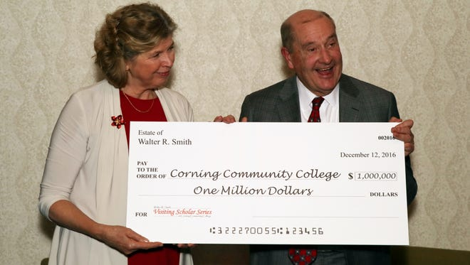 Corning Community College President Katherine Douglas receives a $1 million donation from George Welch Sr., attorney for the estate of Walter R. Smith.