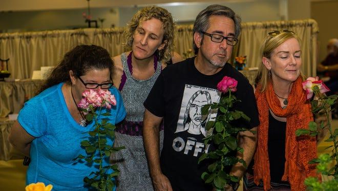 Visitors to a Desert Rose Society event enjoy the fragrance of long-stemmed roses.