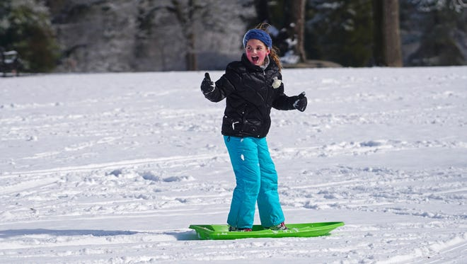 9 year-old Abby O'Connor gives the thumbs up on her successful ride down hill at Rockford Park in February 2017.