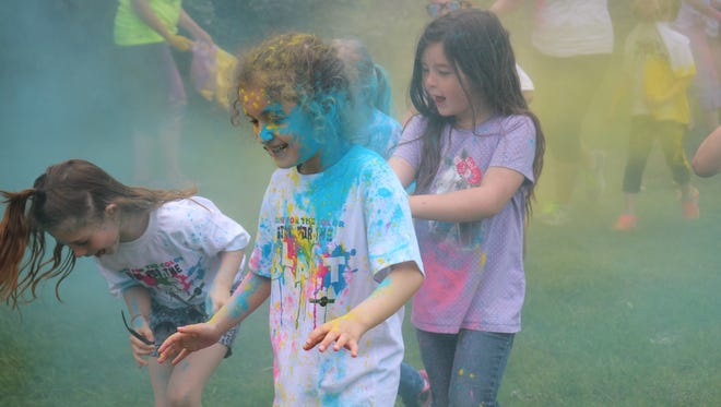 Edgerton Elementary students run through cloudy color during the school's Color-a-thon fundraiser.