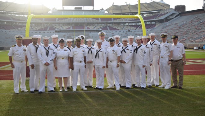 Captain Greg Kercher (left) and 19 sailors from the USS Florida submarine stand on the Florida State field after touring the facilities on Saturday, Nov. 18.
