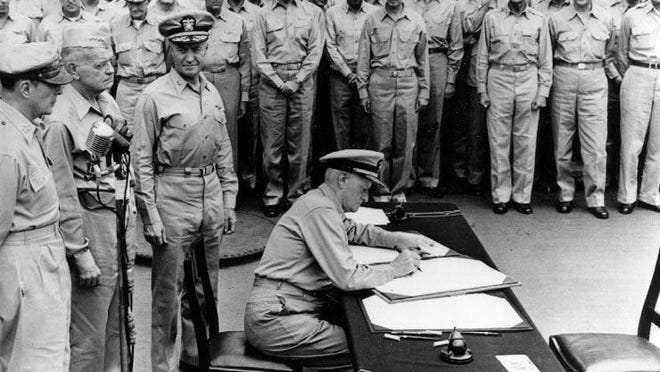 Fleet Admiral Chester W. Nimitz signs the Instrument of Surrender as United States representative aboard USS Missouri on Sept. 2, 1945. Standing behind him are (from left) Army Gen. Douglas MacArthur, Navy Adm. William F. Halsey and  Rear Admiral Forrest Sherman.