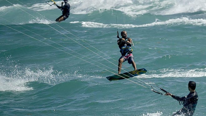 Windy conditions from Hurricane Isaias drew dozens of kite surfers to the beach Saturday in Jupiter.