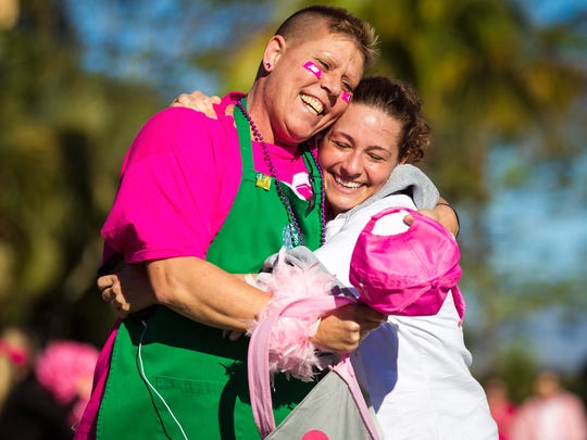 Breast cancer survivor Sue Dundon, left, embraces her Starbucks coworker Bianca Siggia after running the Susan G. Komen Southwest Florida Race for the Cure at Coconut Point mall on Saturday, March 8, 2014, in Estero.