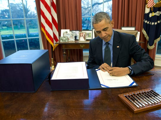 President Barack Obama signs the budget bill in the