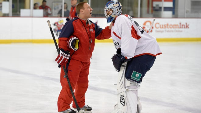 FILE - In this Sept. 18, 2015, file photo, Washington Capitals goaltending coach Mitch Korn, left, talks with Mark Dekanich, right, during media day at NHL hockey training camp in Arlington, Va. The New York Islanders have hired longtime goalie guru Mitch Korn as director of goaltending. Korn rejoins coach Barry Trotz. Korn was director of goaltending with Trotz and the Capitals last season when they won the Stanley Cup. (AP Photo/Nick Wass, File)