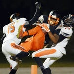 Chauncey Gardner of Cocoa catches a touchdown pass between Booker T. Washington players Dontye Carriere-Williams (15) and Catavis Hudson (14) during last year's Class 4A state semifinal game in Cocoa.