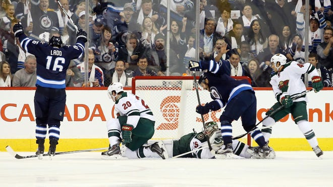 Winnipeg Jets left winger Andrew Ladd (16) celebrates after he puts the puck past Minnesota Wild goalie Darcy Kuemper (35) during the first period at MTS Centre.