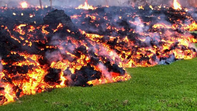 Lava flows across a yard in the Leilani Estates neighborhood of Pahoa, Hawaii, on May 6, 2018.
