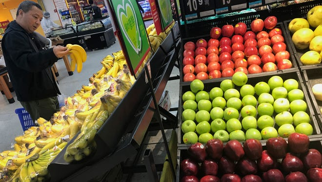 A man chooses bananas near imported apples from the United States at a supermarket in Beijing on Monday.